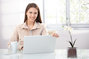 Pretty female using laptop at home smiling