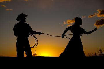 Cowboy couple silhouette catch