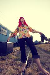 Vintage photo of hippie woman walking on railway barefoot