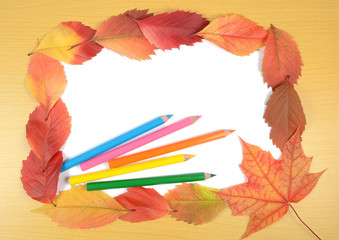 autumn leaves pencils and sheet of paper