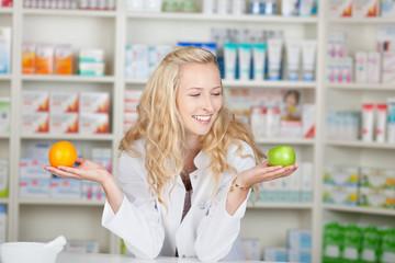 lächelnde apothekerin hält obst in ihren händen