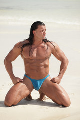 Bodybuilder posing on the sand on his knees
