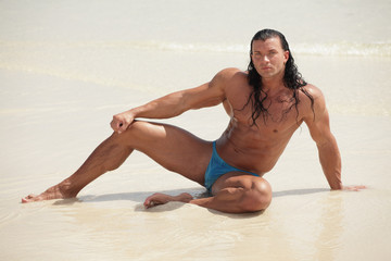 Image of a muscular bodybuilder posing on the sand
