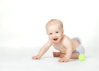 Six month boy sits on the white background and smiles