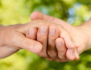 Closeup of senior hands holding together
