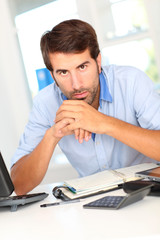 Portrait of office worker sitting at his desk