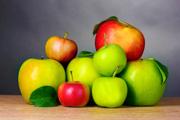 Many fresh organic apples on wooden table on grey background