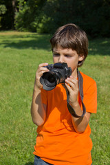 boy taking shots with photocamera in park