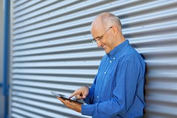 lächelnder mann mit tablet lehnt an der wand