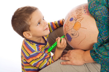 Smiling little son painting the belly of his pregnant mother