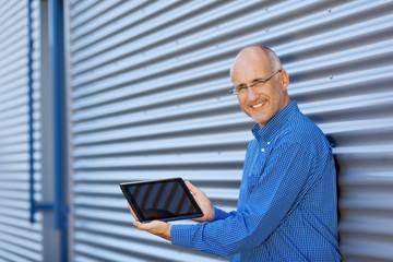lächelnder mann zeigt tablet bildschirm