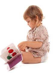 enfant qui regarde un petit livre