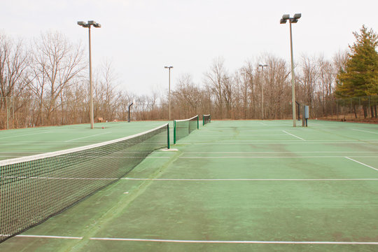 Series of side-by-side tennis courts in a rural resort setting