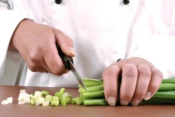 Köchin hält Lauchzwiebeln in ihrer Hand und schneidet das Gem