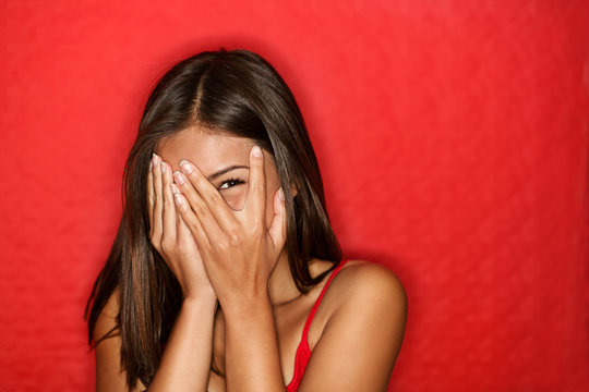 Playful shy woman hiding face laughing