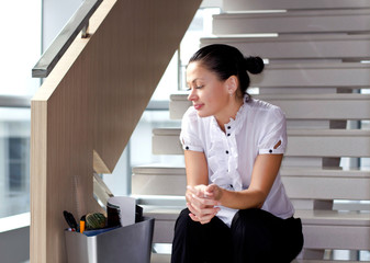 Downsizing, sad business woman Sitting on Stairs