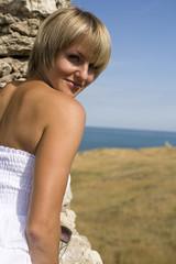 beautiful young woman near old wall