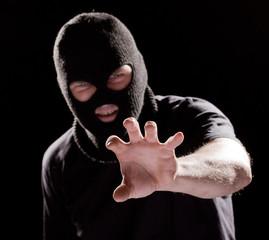 Burglar in mask, robbing something by  hand