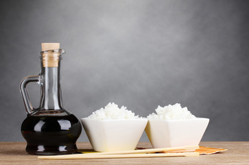 Bowls of cooked rice and soy sauce in jar