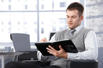 Businessman writing notes to personal organizer