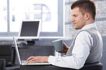 Young man working in office using laptop