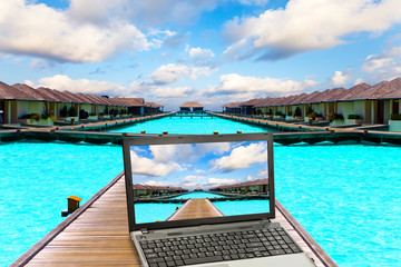 Wooden road  over the sea and the laptop with a beach picture..
