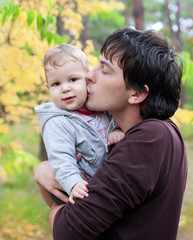 dad kissing his son on autumn outdoor