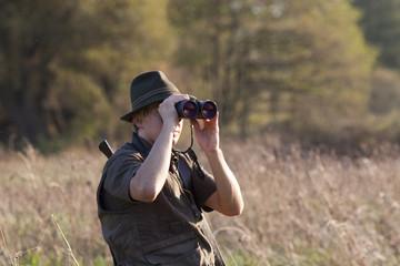 Jäger mit Fernglas und Waffe