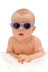 Funny baby in sunglasses  lying on the blanket - isolated