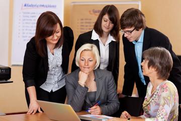 arbeitsgruppe schaut auf laptop