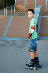 Boy with roller blades in front of a ramp