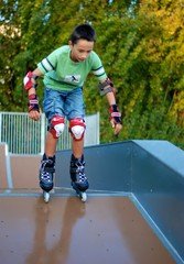 Boy roller blading down from a ramp