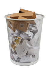 silver mesh office wastebasket full of paper, isolated on white