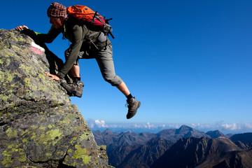 Young man climbing the mountain ridge Wall mural