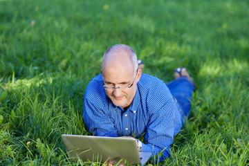 mann mit laptop liegt entspannt auf einer wiese