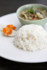 Thai food chicken green curry with rice in wood background