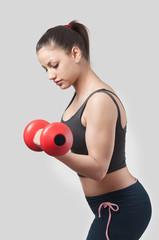 Strong attractive girl exercising with weights.