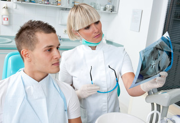 woman dentist and patient looking at x-ray image