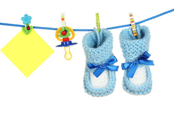 baby socks and booties on a rope isolated on white