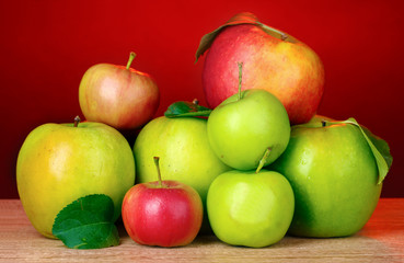 Many fresh organic apples on wooden table on red background