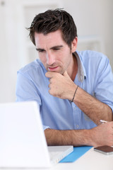 Office worker with thoughtful look in front of laptop