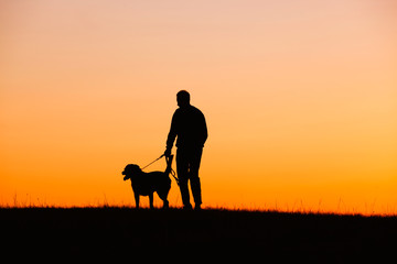 Man with a dog, at sunset