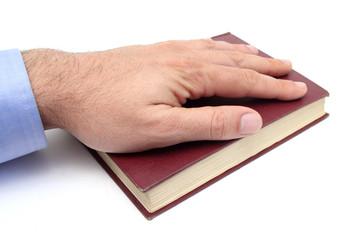 closeup of a hand swearing on a bible