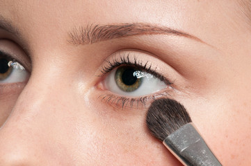 Woman applying cosmetic paint brush on eye zone