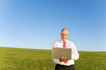 lächelnder mann mit laptop auf einer wiese