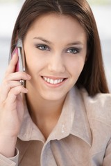 Closeup portrait of smiling woman on phone
