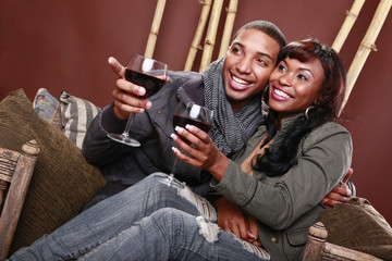 Young couple enjoys red wine at the bamboo foyer