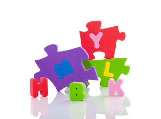 colorful alphabet foam puzzle pieces isolated over white backgro