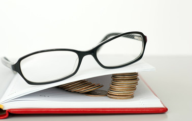 Glasses, book and coins
