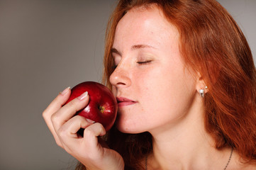 young red hair woman with red apple